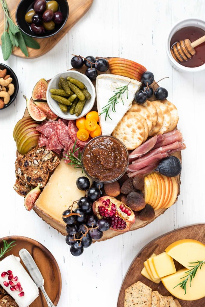 Cheese board filled with a variety of meats, cheeses, fruit and crackers