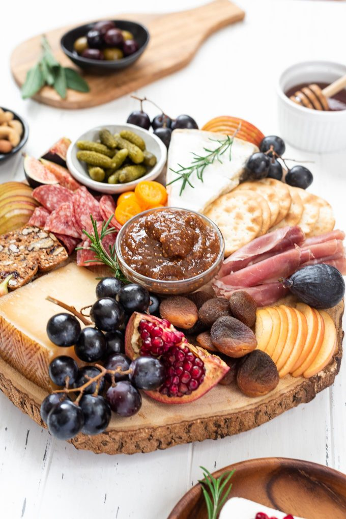 Close up of cheese board filled with cheese, meats, crackers and fruit
