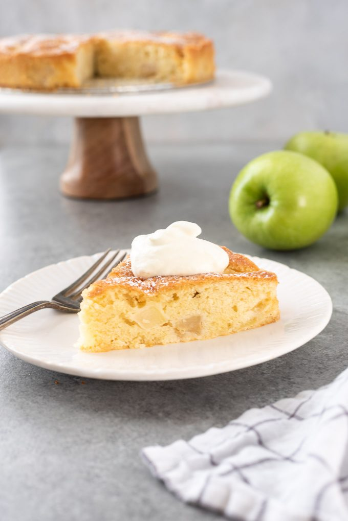 french apple cake on a plate topped with whipped cream
