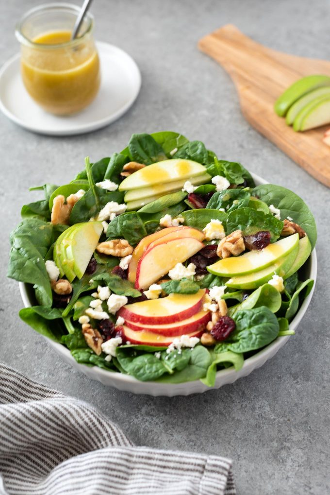 Spinach Apple Salad in a bowl with dressing in background