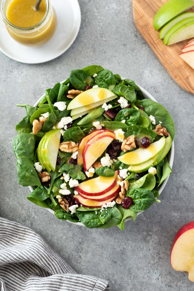 Spinach and apple salad in a bowl with dressing behind