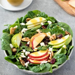 Close up of Spinach Apple Salad in white bowl