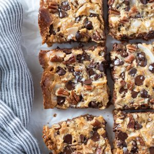 Seven layer magic cookie bars on parchment paper