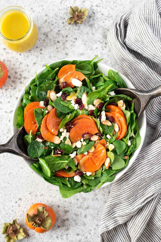 Persimmon salad in a bowl with salad servers