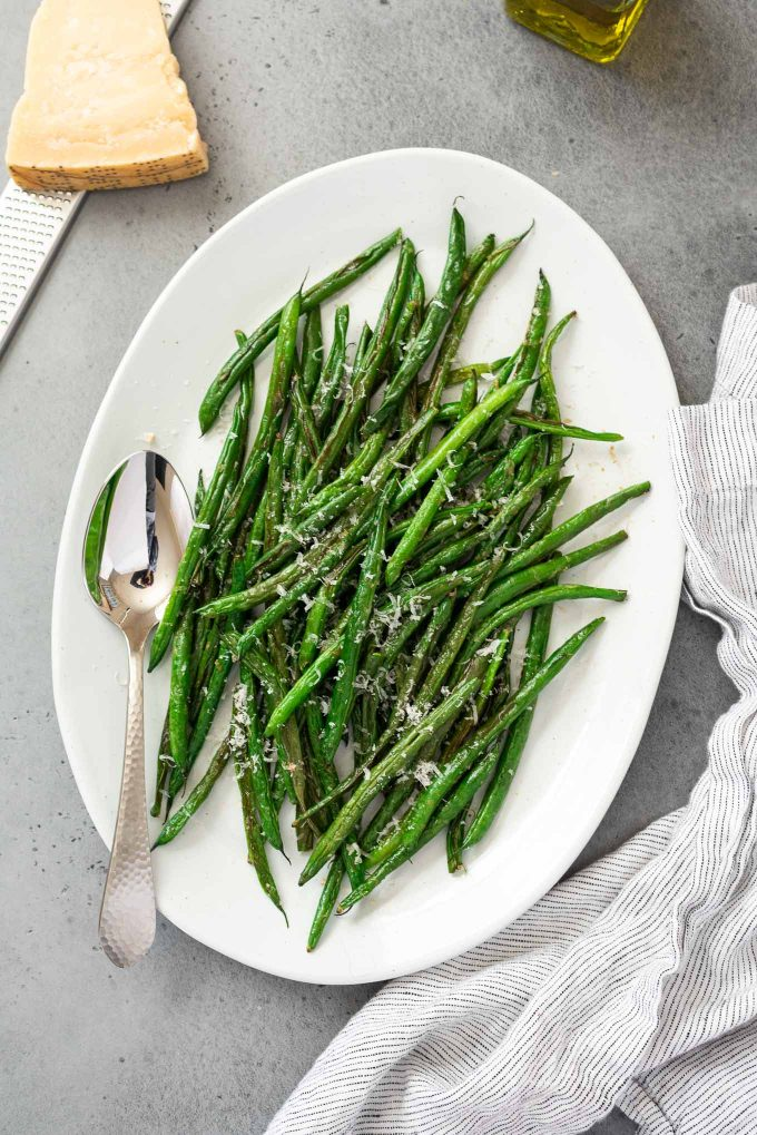 platter of roasted green beans with a spoon and linen