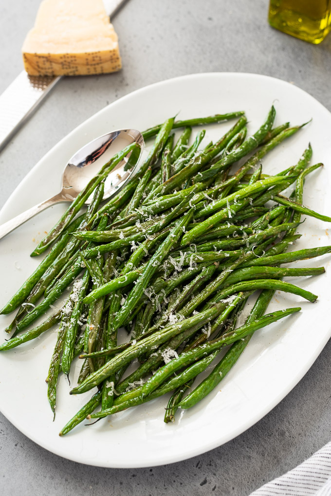 Roasted green beans on a platter topped with parmesan cheese