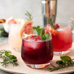 Vodka Spritzers on a server with herbs and cocktail shaker