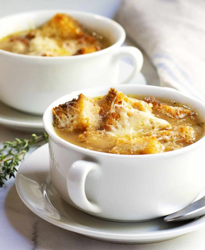 French onion soup in a mug with croutons on top