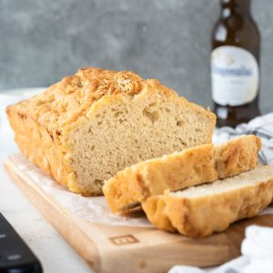 Loaf of beer bread sliced on a cutting board