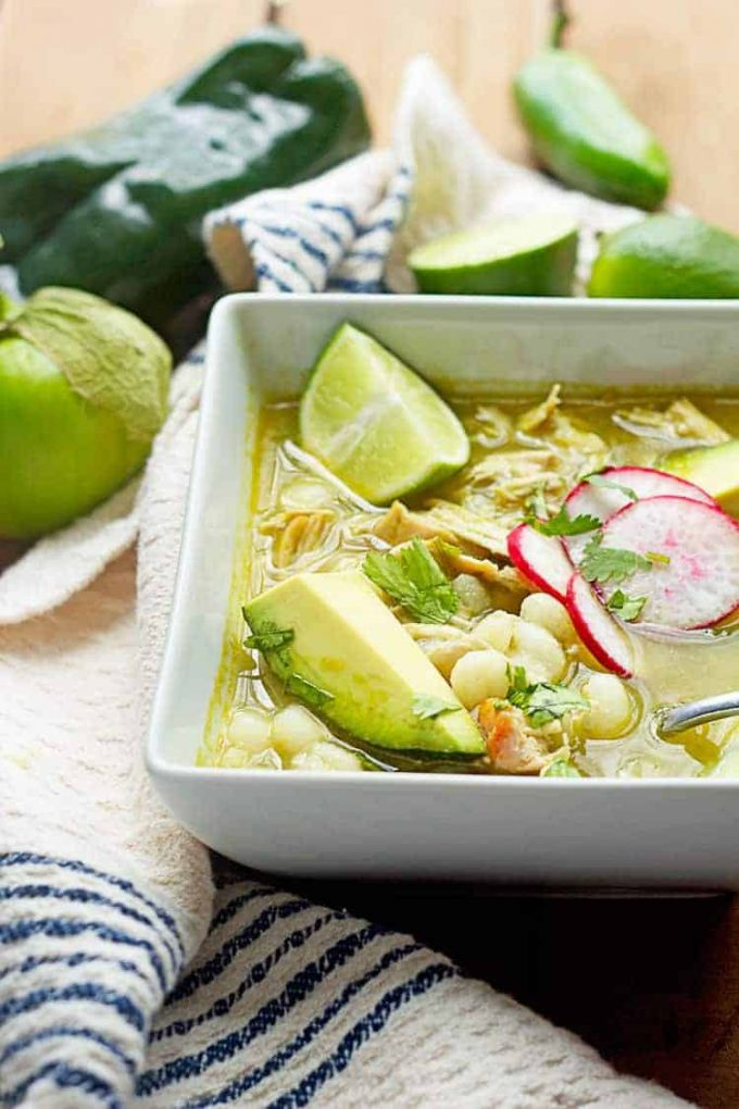 Mexican chicken pozole verde soup in a bowl with avocado