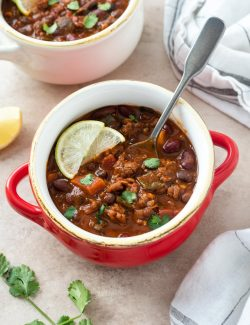 Chorizo chili in a red bowl with lime and cilantro