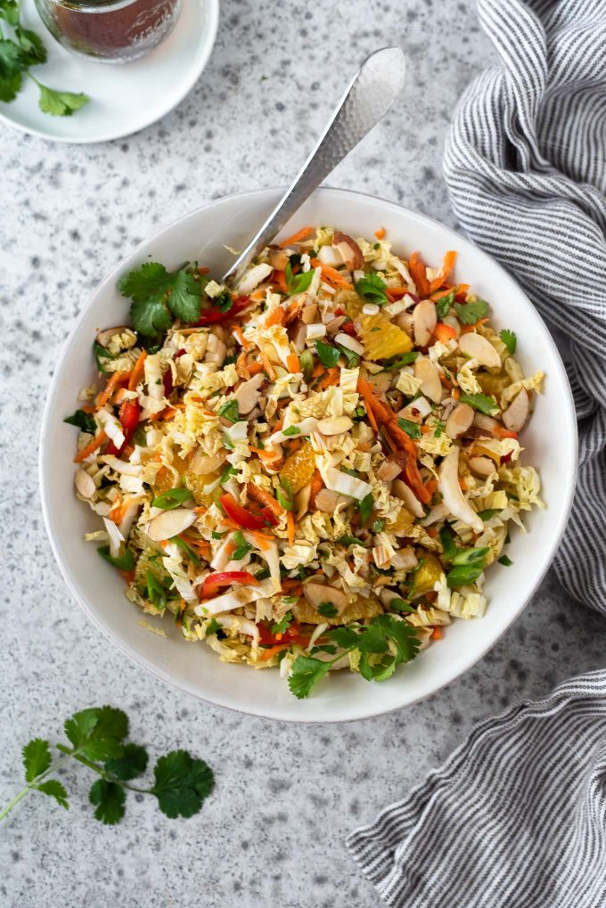 Napa cabbage salad in a white bowl with spoon
