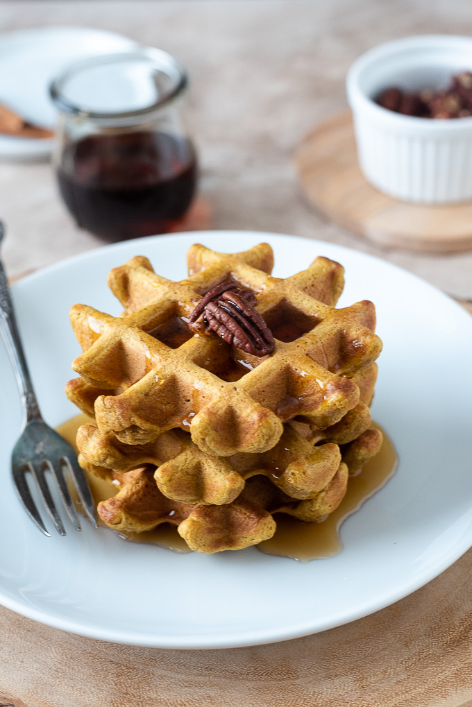 Stack of sweet potato waffles with pecans and maple syrup