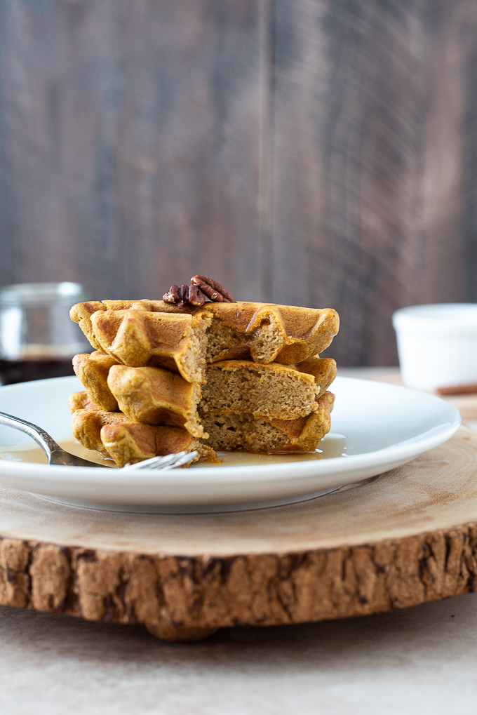 Stack of sweet potato waffles cut with syrup dripping down