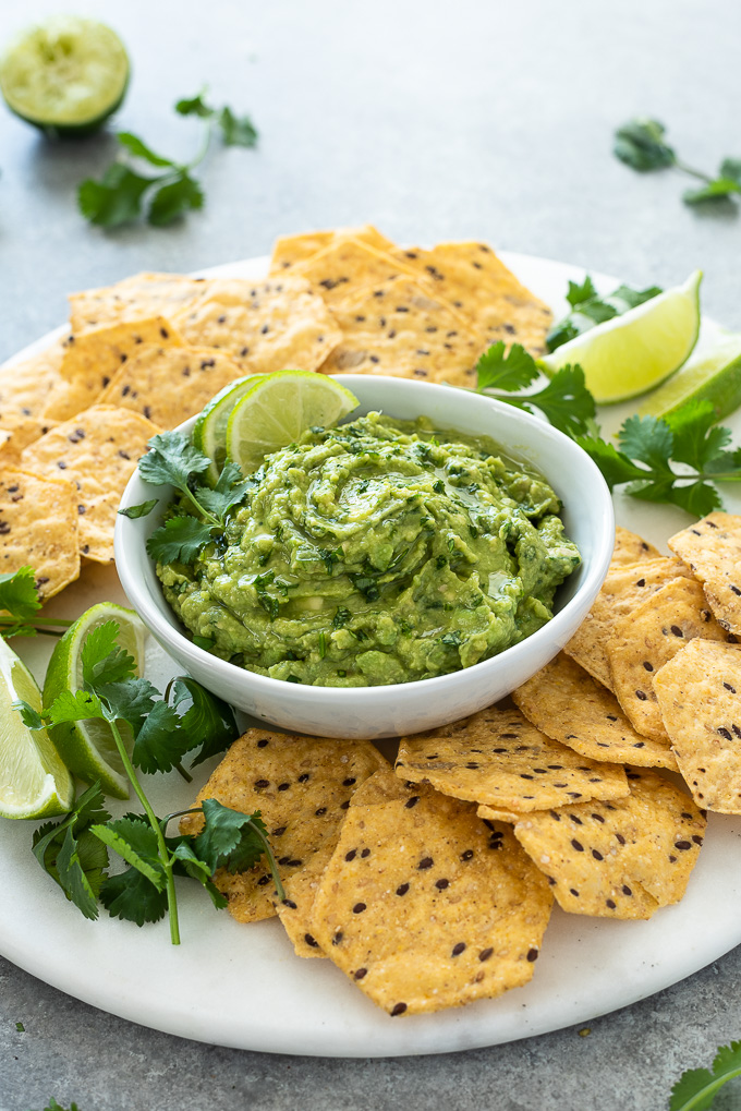 Homemade guacamole in white bowl with lime and cilantro