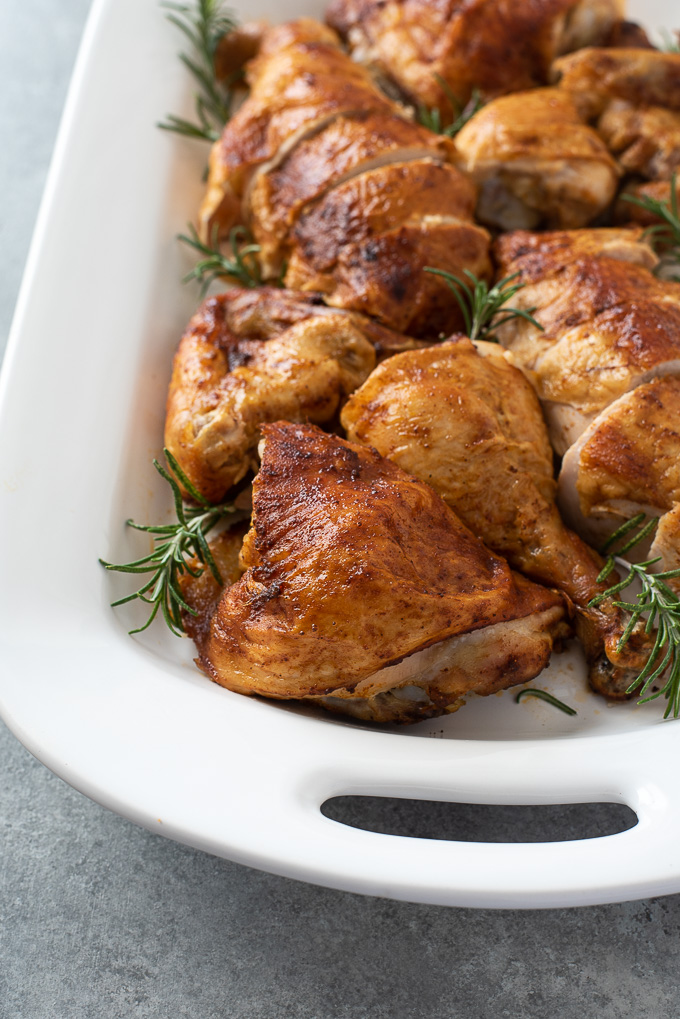Carved spatchcock chicken on platter with rosemary