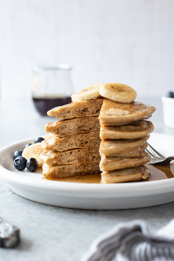 Stack of oat flour banana pancakes with syrup dripping down