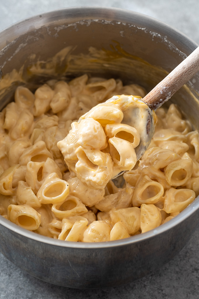 Spoonful of creamy mac and cheese over a pot