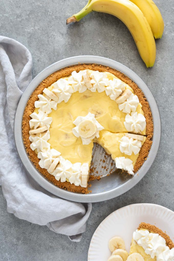 Banana cream pie with serving on a plate nearby