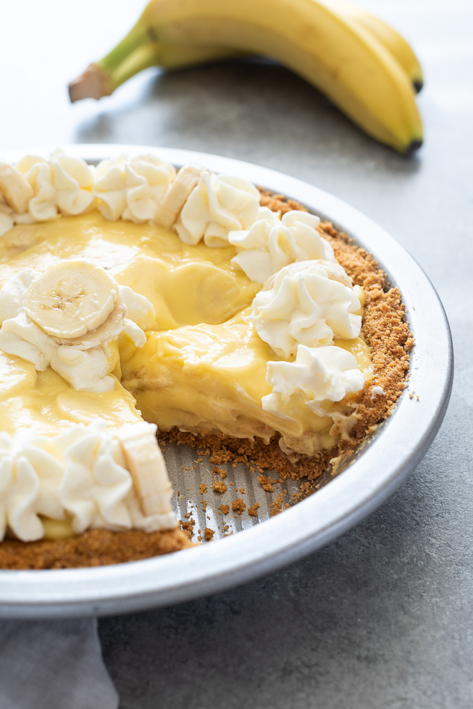 Banana cream pie in pan with whipped cream and bananas on top