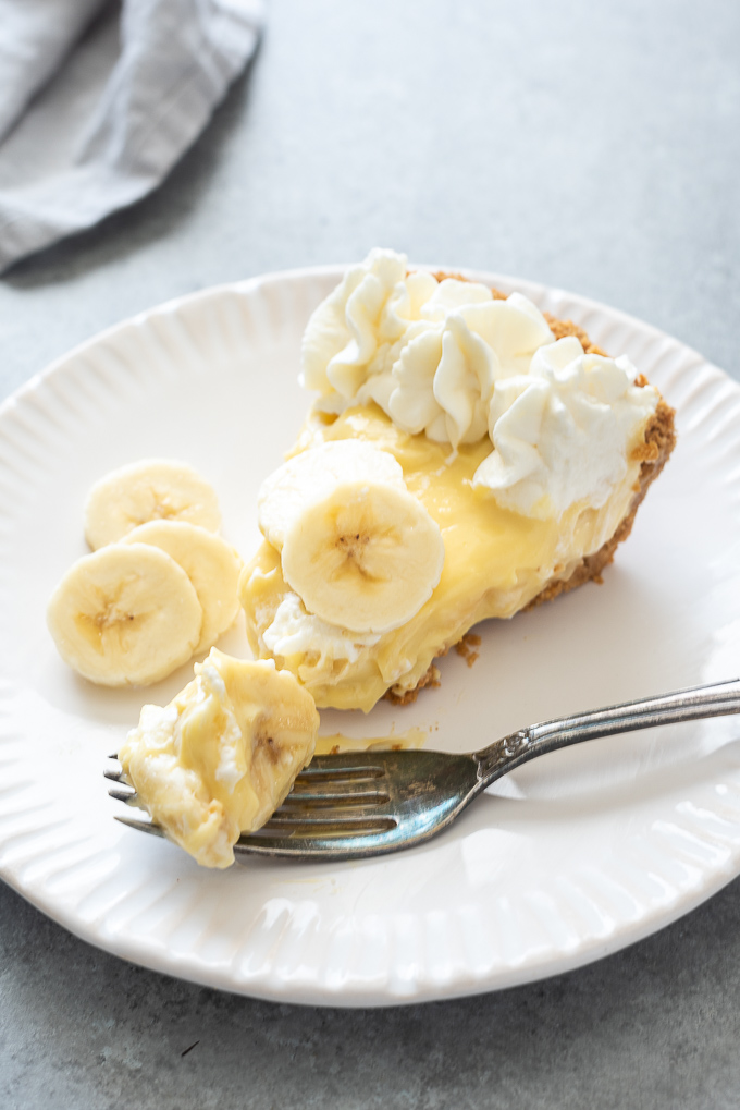 Slice of banana cream pie on a white plate