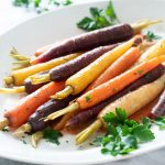 Maple glazed carrots on a platter with fresh parsley