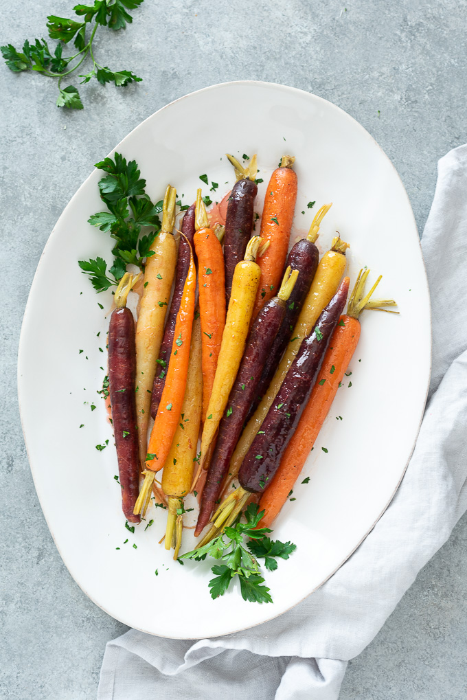 Glazed carrots on a white serving dish with a linen alongside