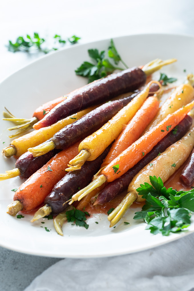 Glazed carrots on a white serving plate with fresh parsley