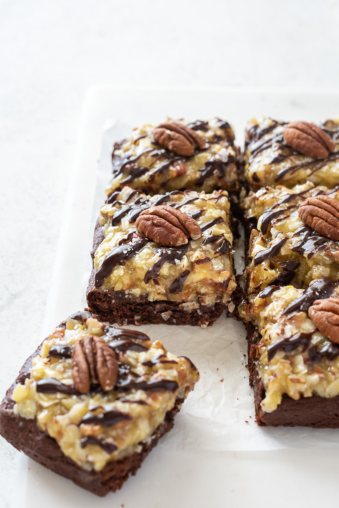 German chocolate brownies cut into squares with pecan halves on top