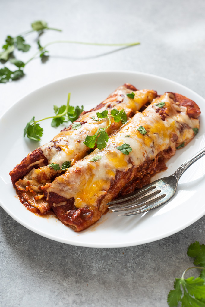 Two chicken enchiladas on a white plate with cilantro