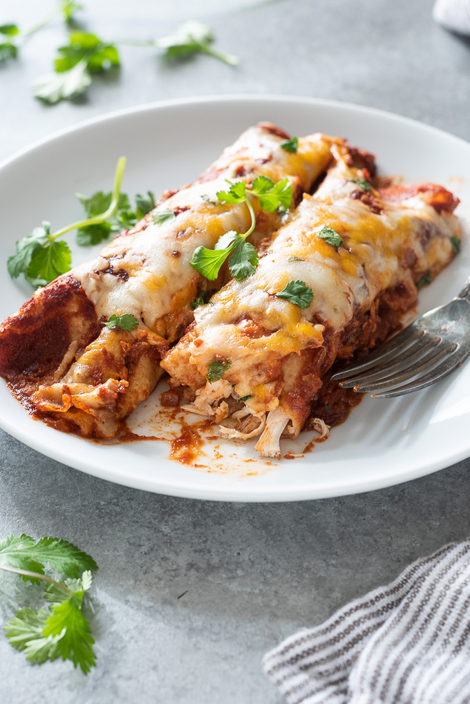 Chicken enchiladas on a plate with bite out of one