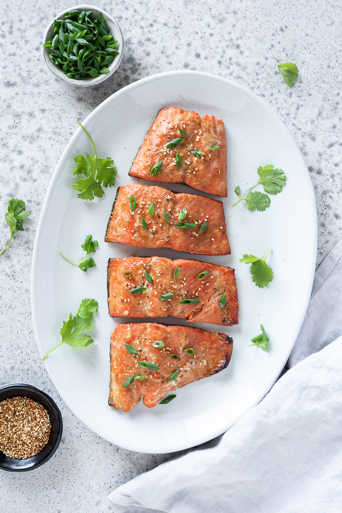 Miso marinated salmon on a platter with sesame seeds and scallions