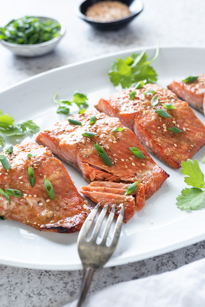 Miso marinated salmon on a platter with fork flaking fish
