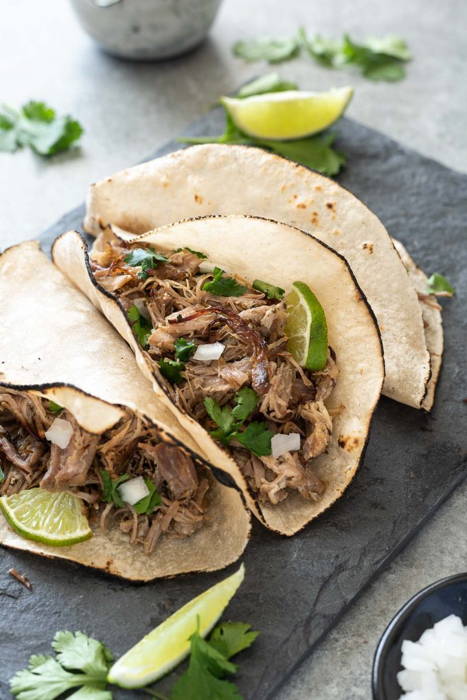 Slow Cooker Pork Carnitas in tortillas with onion, cilantro and lime