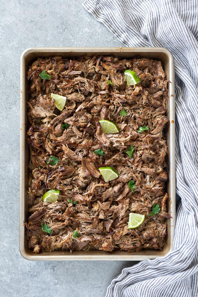 Baking sheet with shredded pork carnitas, lime and cilantro