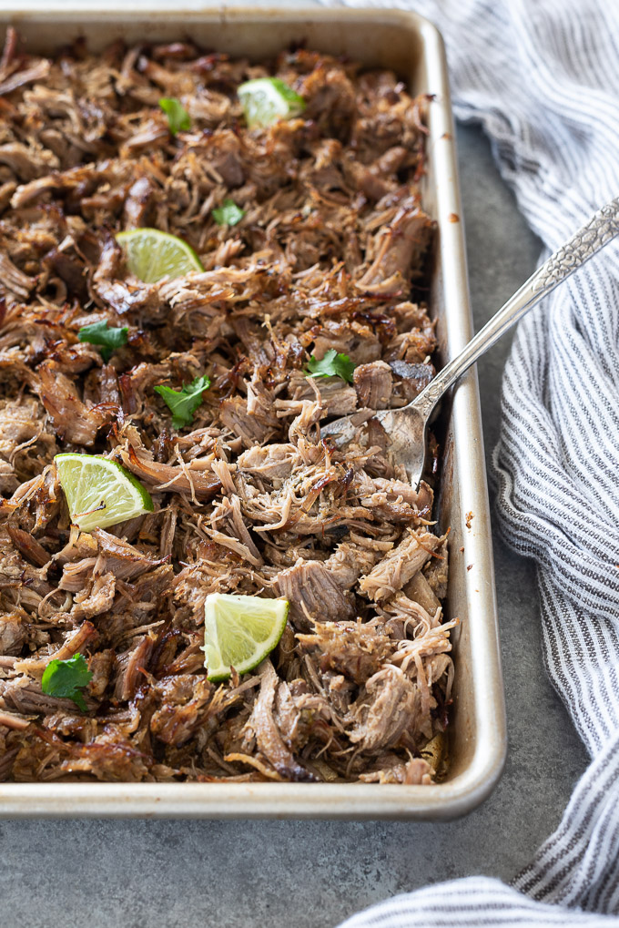 Spoon full of shredded pork carnitas on a baking sheet