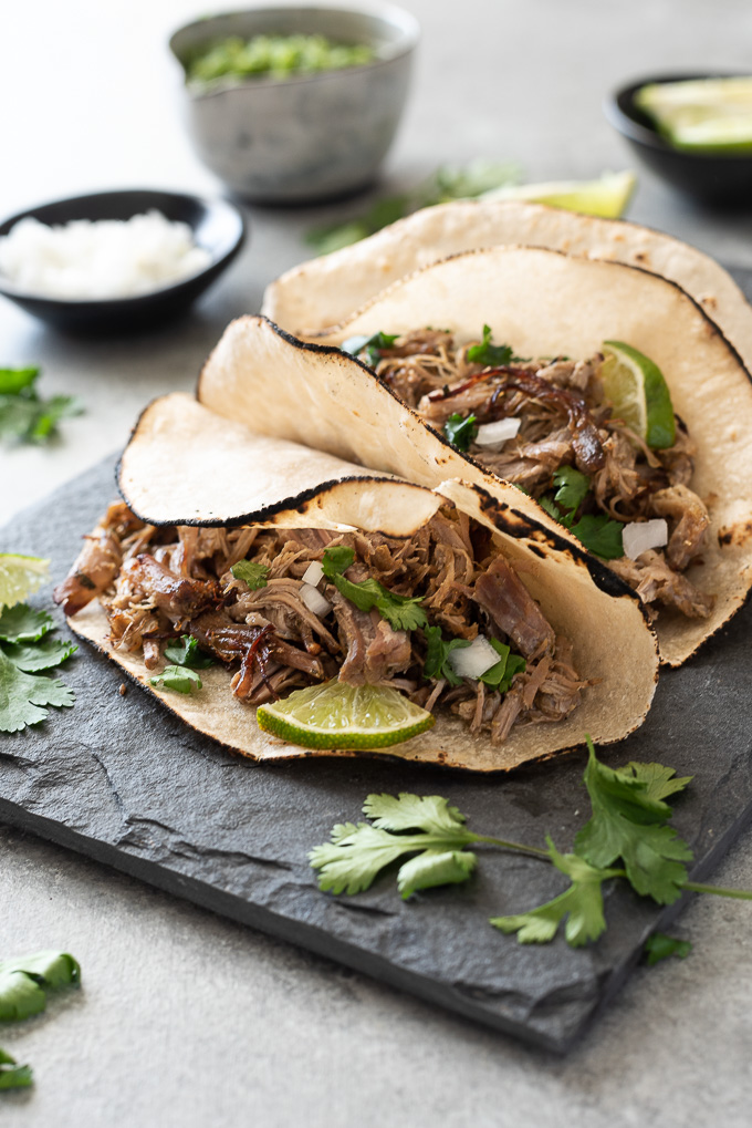 Slow cooker pork carnitas tacos on plate with diced onion, cilantro and lime