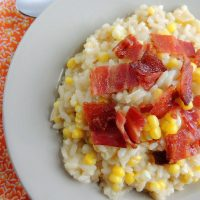 Overhead view of bacon and corn risotto in a white dish.