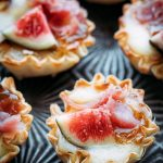 Close up shot of phyllo brie bites topped with figs.