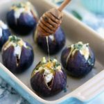 Figs stuffed with goat cheese being drizzled with honey. The figs are in a blue baking dish.