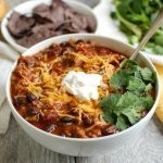 A large bowl of beef poblano chili topped with sour cream, cheese, and cilantro.