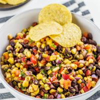 A bowl of black bean and corn salsa with three tortilla chips.