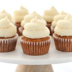 A white cake stand topped with carrot cake cupcakes.