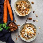 Overhead view of two bowls of carrot cake granola next to fresh carrots and a dish of pecans.