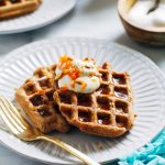 Two carrot cake waffles on a white plate.