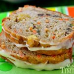 Two slices of glazed carrot apple zucchini bread stacked on each other.