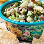 A floral bowl of corn and bacon salsa surrounded by tortilla chips.