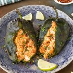 Two cream cheese stuffed poblano peppers on a blue plate.