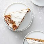 Two slices of dairy free carrot cake on white plates.