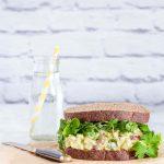 An egg salad sandwich next to a jug of water.